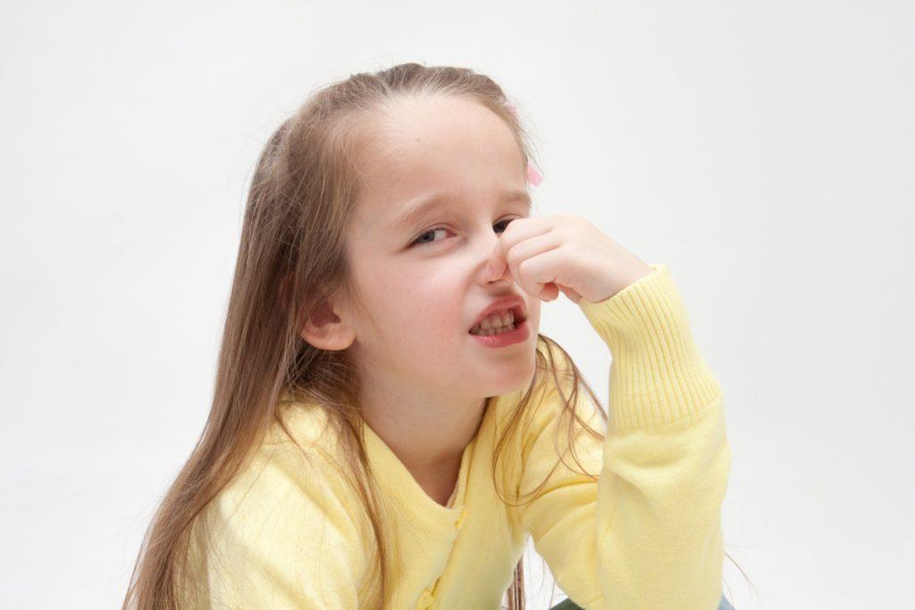 鼻をつまむ少女